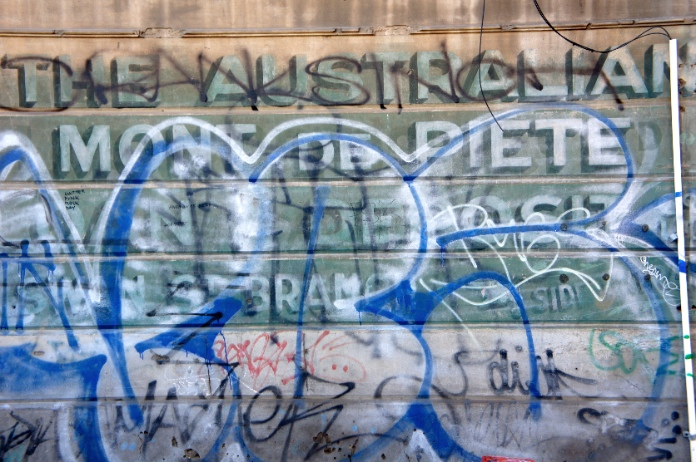 Layers of graffiti and old advertising on brick wall